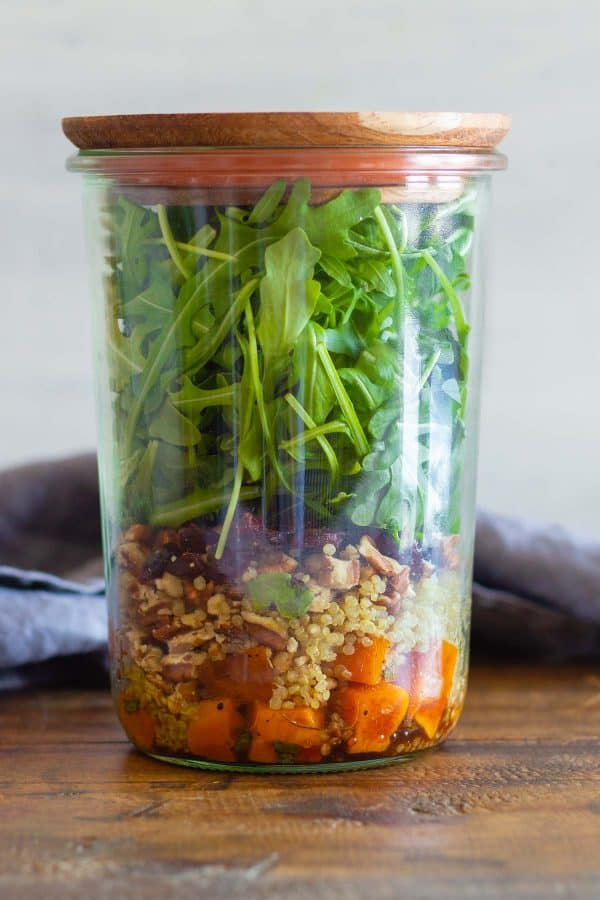 Butternut squash salad in a tall glass jar with wooden lid