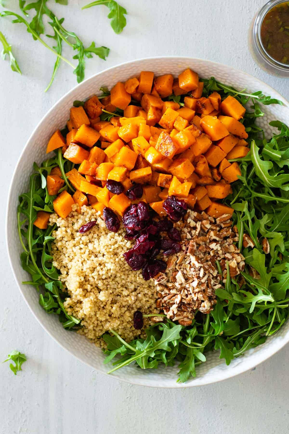 Salad bowl with arugula, roasted butternut squash, quinoa, pecans, and dried cranberries