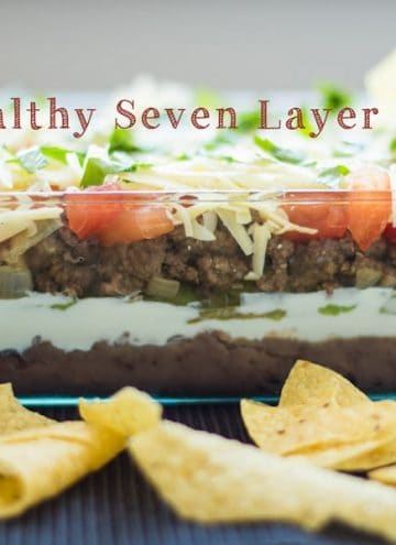 Healthy Seven Layer Dip viewed from the side with tortilla chips.