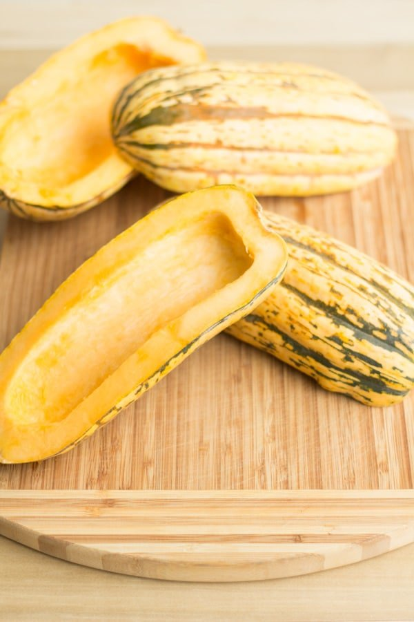 Halved Delicata Squashes on a chopping board