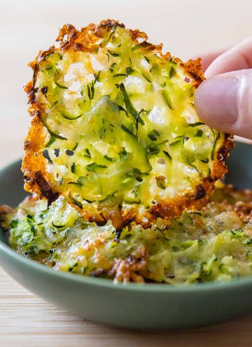 Zucchini cheese crisp being lifted off a plate.