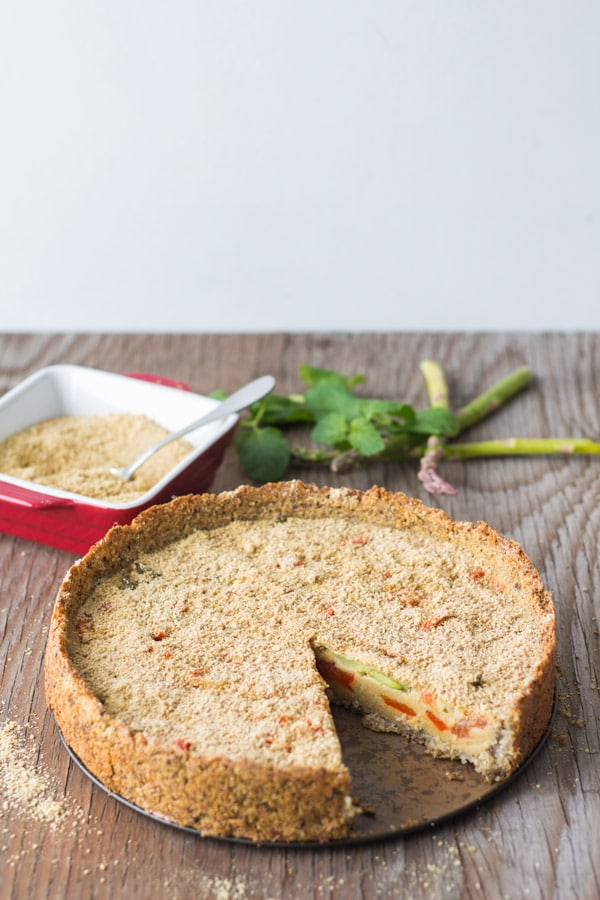 Flourless Vegan Vegetable Quiche missing a slice on a wooden board.