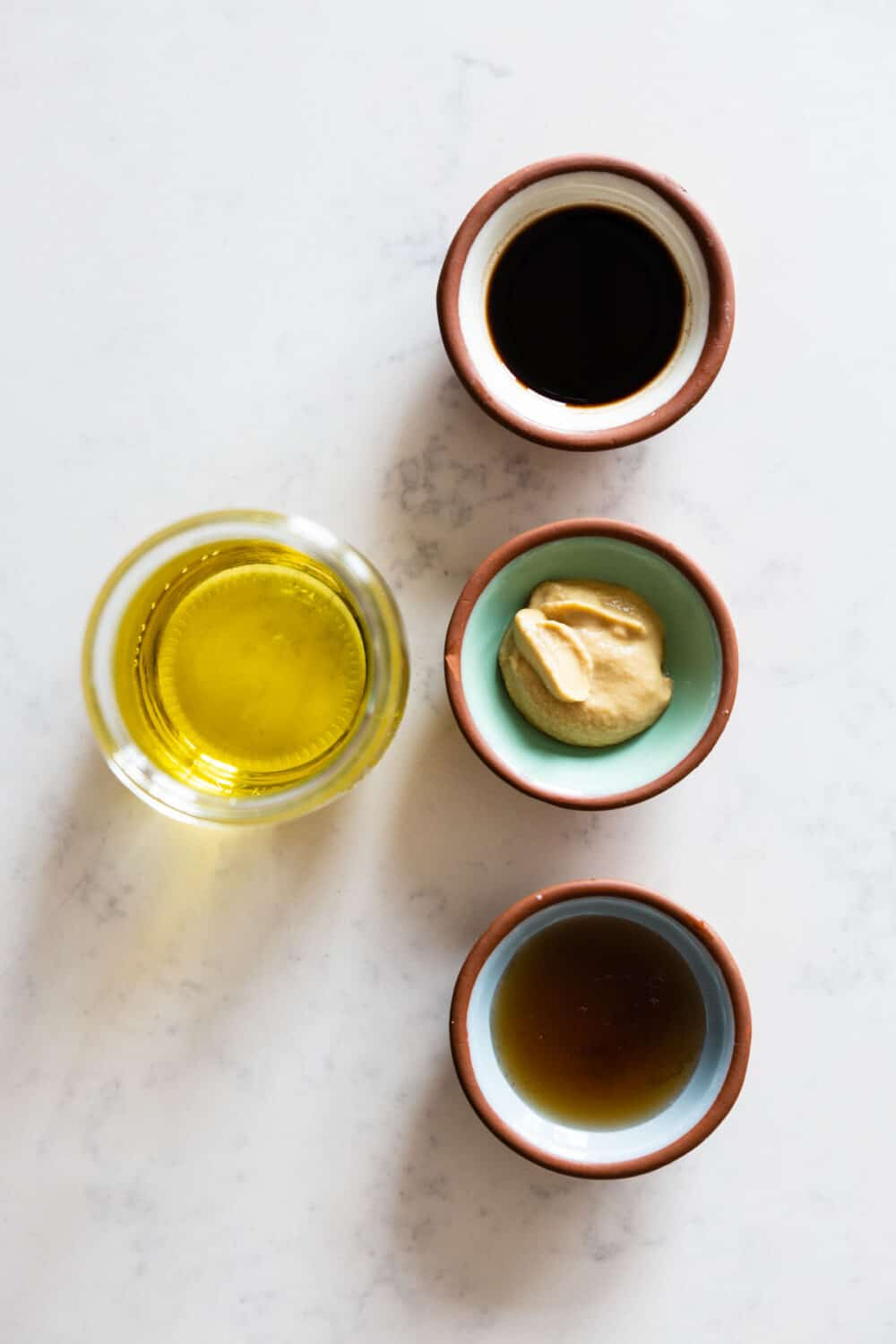Ingredients for Maple Mustard Balsamic Dressing laid out on a kitchen counter.