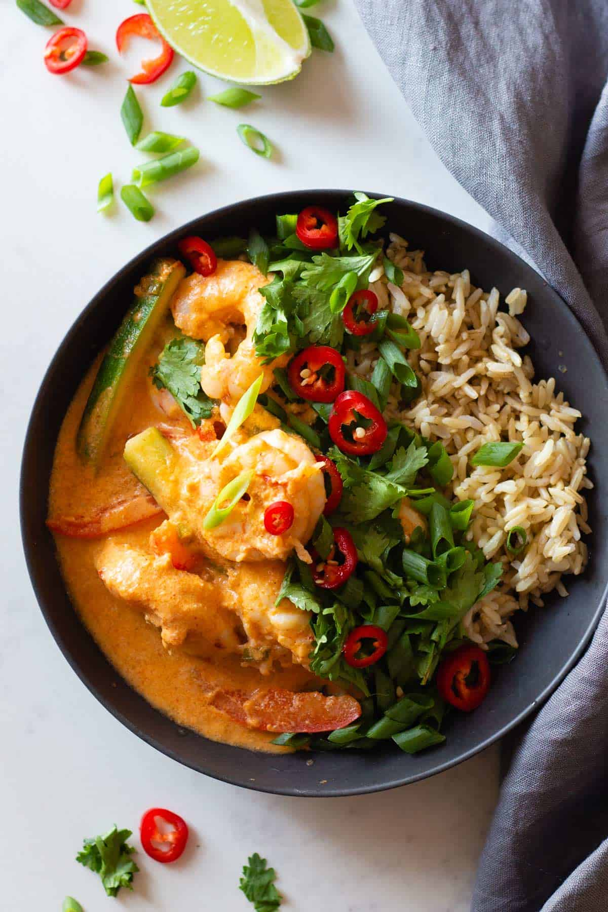 Coconut Shrimp Curry and brown rice in a grey bowl topped with herbs and chili.