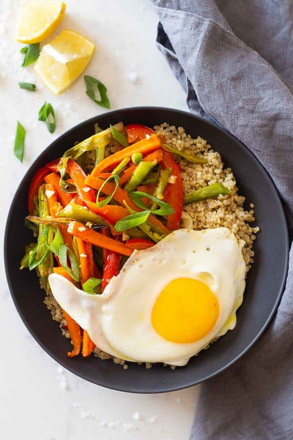 A grey bowl of quinoa, roasted vegetables, and a fried egg.
