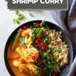 Coconut Shrimp Curry in a bowl with brown rice and text overlay with recipe title for Pinterest.