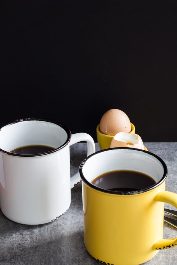 Two cups of Cafe de Olla and an egg in the background.
