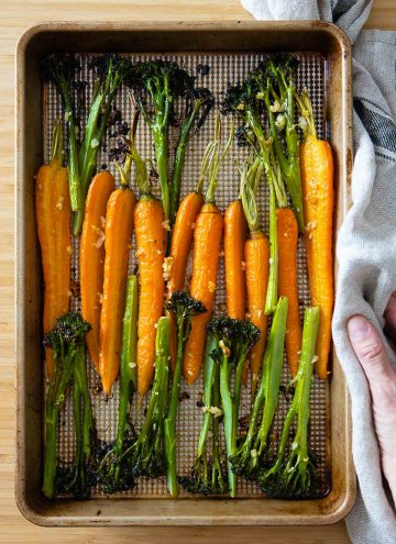 Roasted carrots and broccolini on a baking sheet.