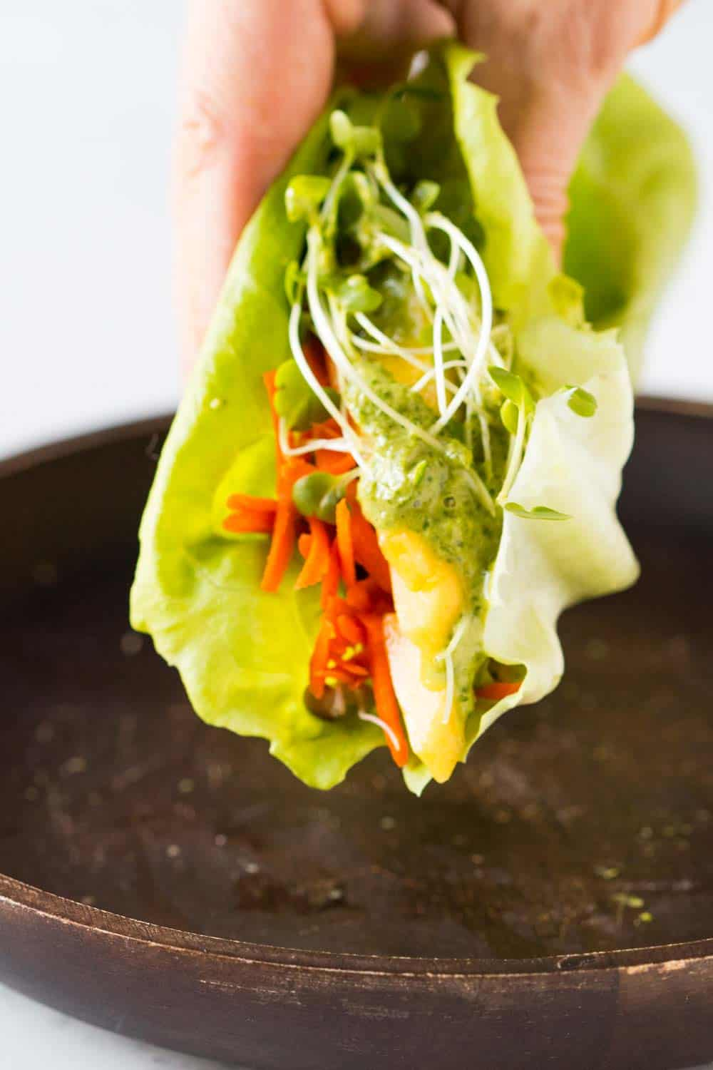 Close up of lettuce wrap with green sauce.