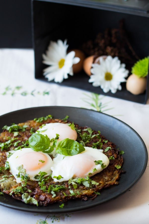 Swiss Roesti with Perfect Poached Egg garnished with herbs served on a black plate.