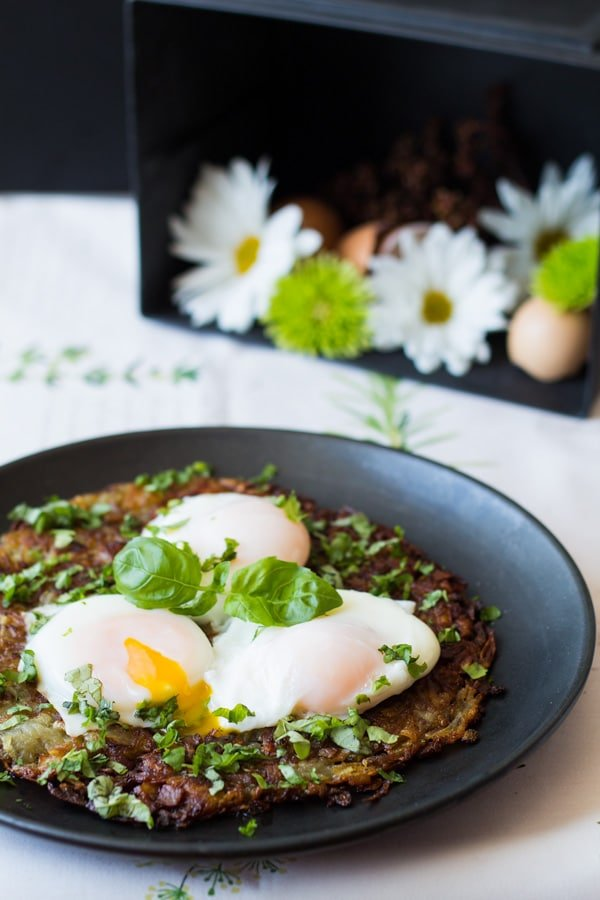 Swiss Roesti with Perfect Poached Egg with egg yolk running served on a black plate.