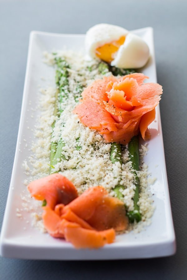 Asparagus with parmesan cheese, salmon shaped in flowers, and a hardboiled egg cut in half on a long white rectangular plate.