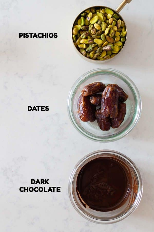 A measuring cup with shelled pistachios, a glass bowl with dates, a glass bowl with melted chocolate and text overlay naming each ingredient.