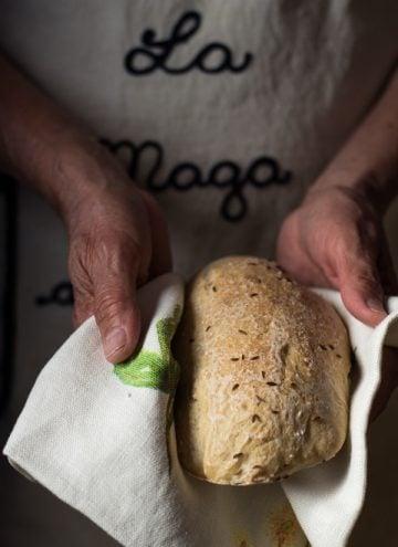 Authentic German Bread held in a kitchen towel in hands