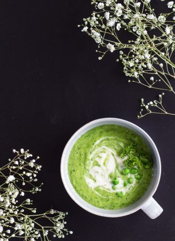 Top view of Simple Green Pea Soup on a black background with small flowers.