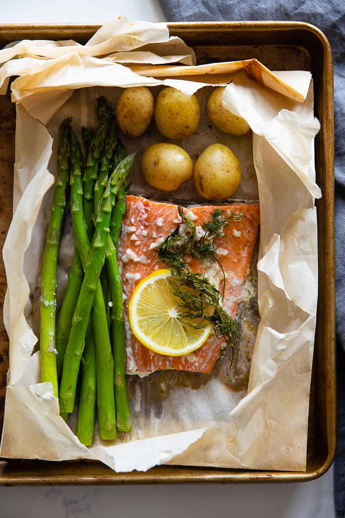 Asparagus, salmon, baby potatoes, a slice of lemon and dill in a ripped parchment paper bag on a baking sheet.
