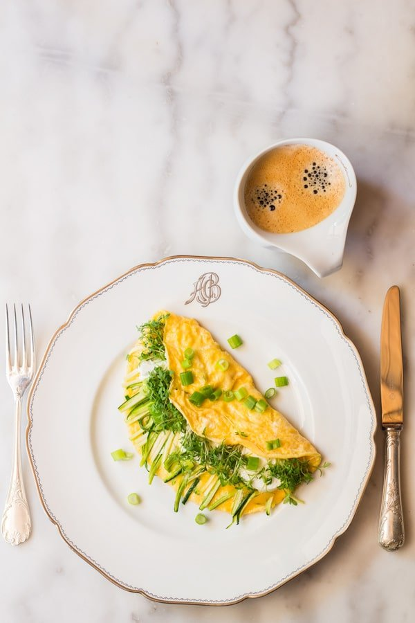Top view of Goat Cheese Omelette on a plate with a fork and knife, and a cup of coffee.
