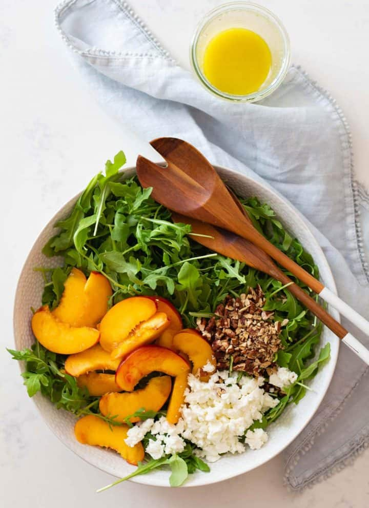 sliced nectarine, crumbled feta, chopped pecan on arugula in salad bowl