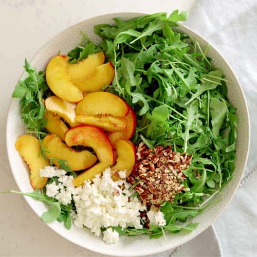 assembled nectarine arugula salad with feta and pecans