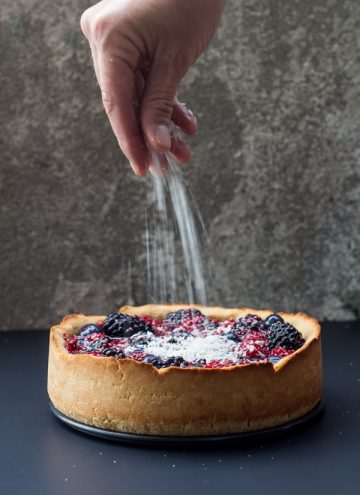 Hand sprinkling sugar on a Healthy Berry Cake.