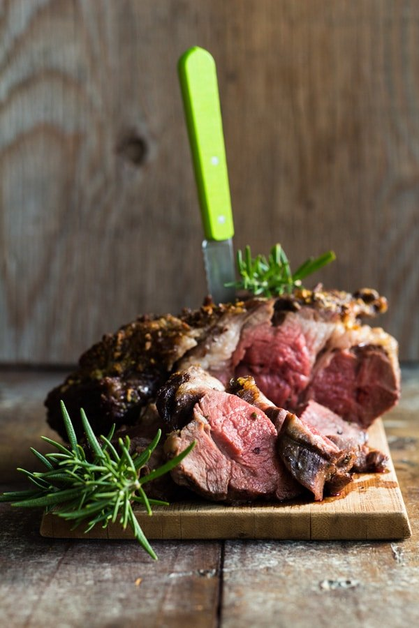 Boneless lamb shoulder roast with rosemary sprigs served on a wood board, and a knife inserted on top.