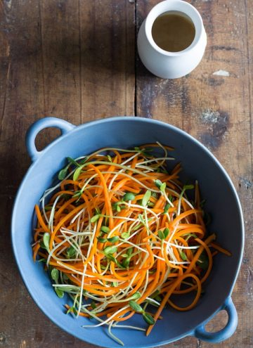 Top view of Sunflower Carrot Salad in a blue bowl with a white dressing jar on a wooden board.