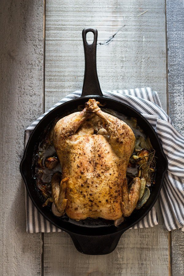 Easy Roast Chicken in skillet with a striped napkin underneath on a rustic wood board.