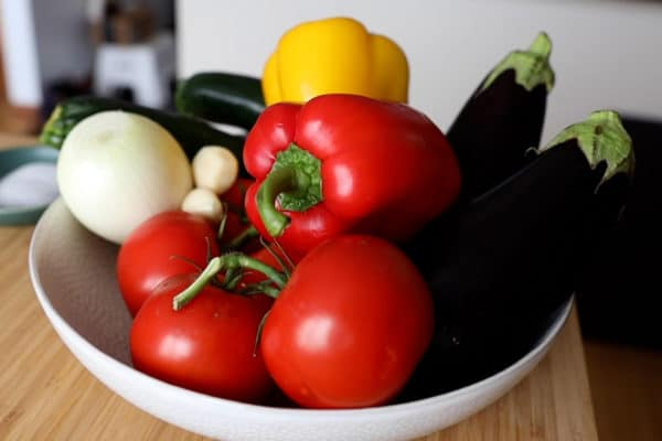 Tomatoes, bell peppers, eggplants, zucchinis, onion, garlic in a white bowl.
