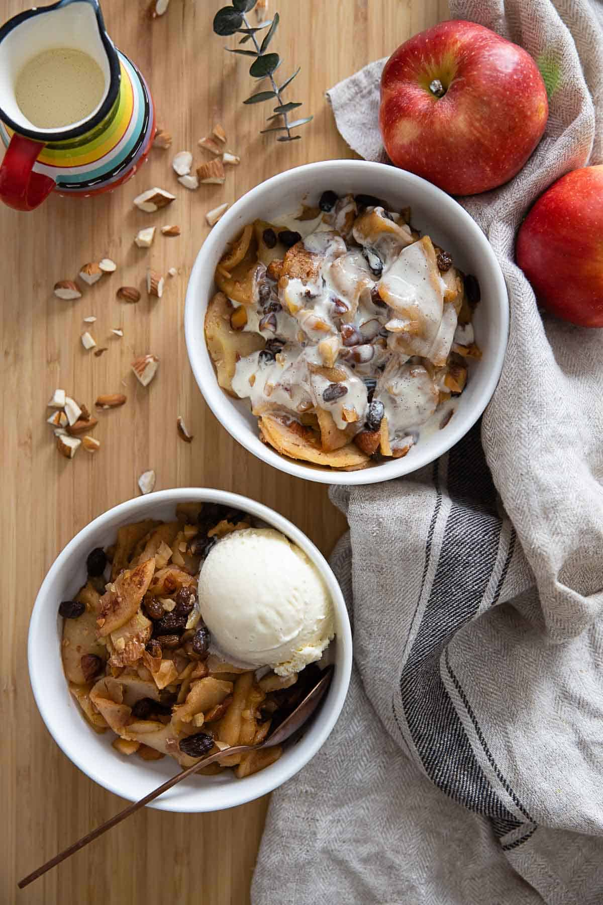 Two bowls of sliced baked apples one topped with custard the other topped with a scoop of vanilla ice cream.