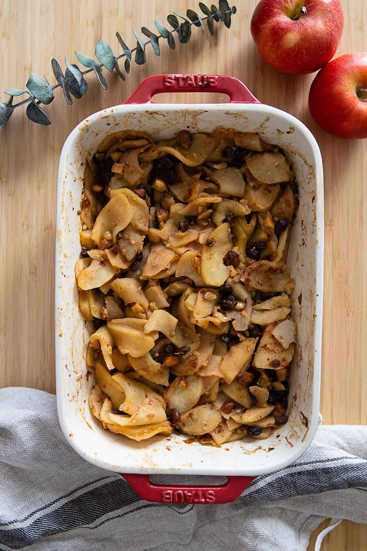 Sliced baked apples in a red baking dish.
