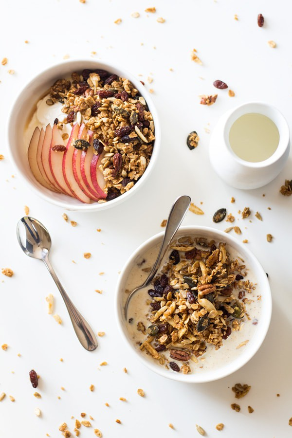 Healthy Homemade Granola in a bowl with milk and a spoon, and topping another bowl of yogurt and sliced apple. A spoon and milk jar next to it.