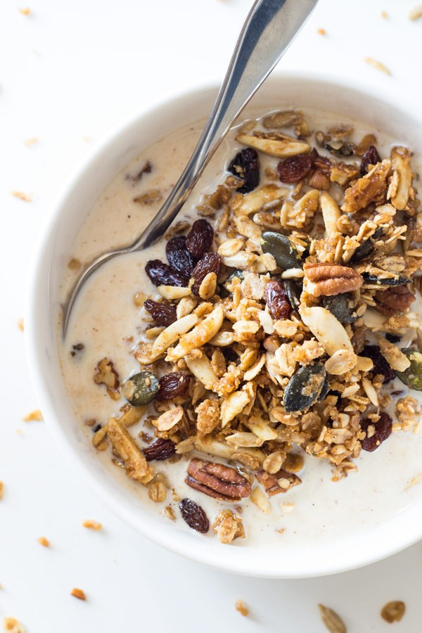 Top view of a bowl of Healthy Homemade Granola with milk and a spoon.