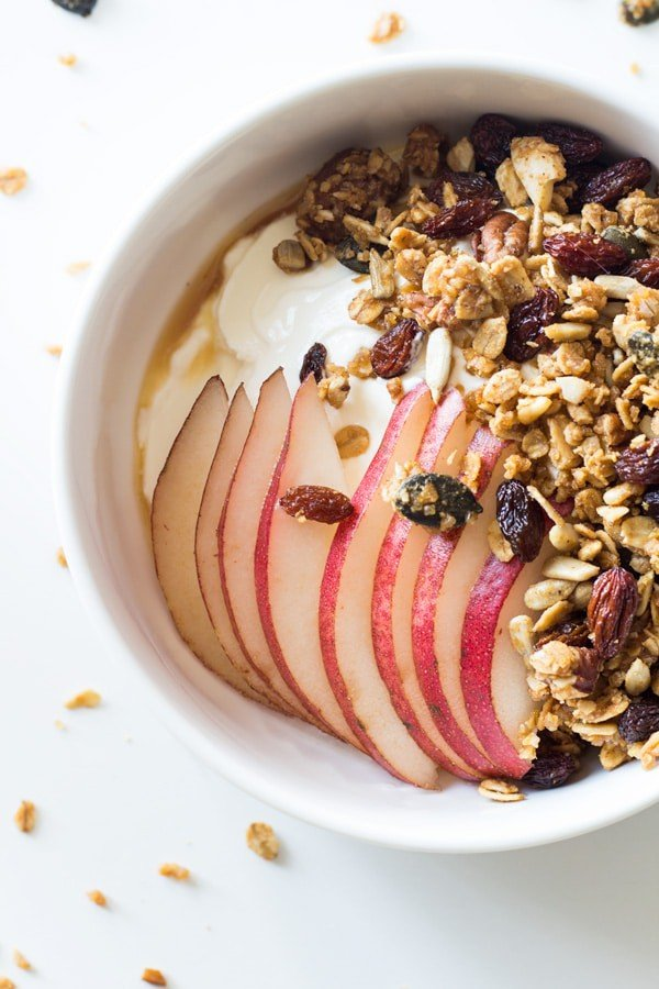 Top view of a bowl of yogurt topped with Healthy Homemade Granola, sliced apples and honey.