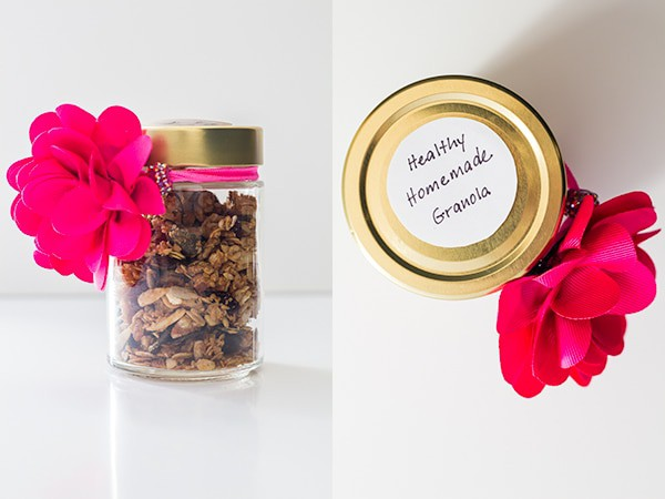 Gift glass jar with Healthy Homemade Granola decorated with a pink flower bow and a written sticker.