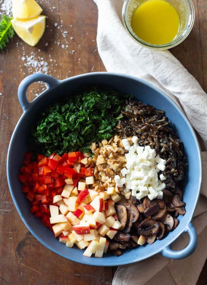 Unmixed wild rice salad ingredients in a blue salad bowl.