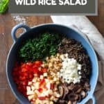 Unmixed wild rice salad ingredients in a blue salad bowl with text overlay of title for Pinterest.