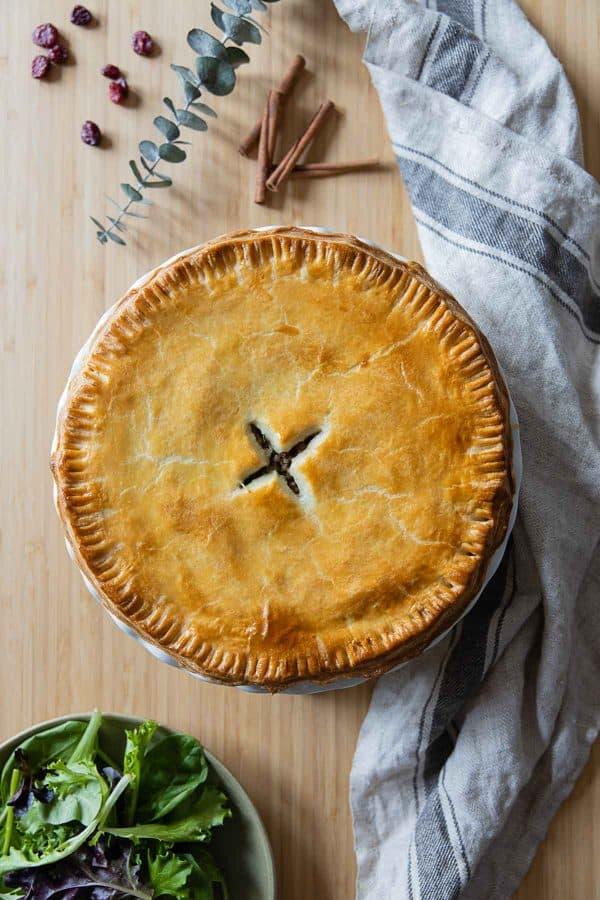 Whole, uncut, Tourtière meat pie on a kitchen counter.