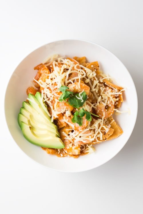 A bowl of Mexican Breakfast Chilaquiles con Camarones with shredded cheese and avocado slices.