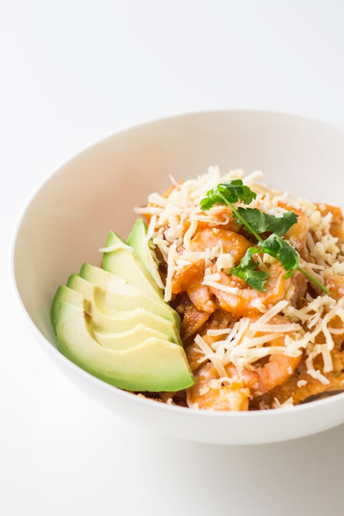 Close up of a bowl of Mexican Breakfast Chilaquiles con Camarones with shredded cheese and avocado slices.