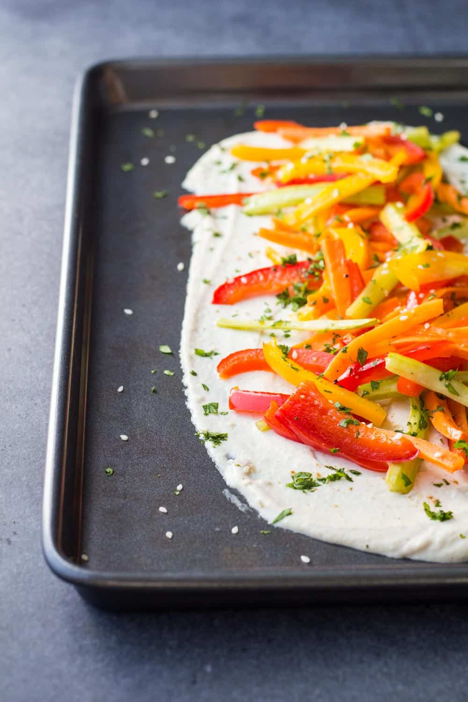 Greek Yogurt Tahini Dip with Roasted Veggies on a baking sheet sprinkled with coriander.