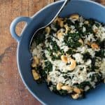 Leftover Rice with cashews and kale in a blue bowl with a spoon.