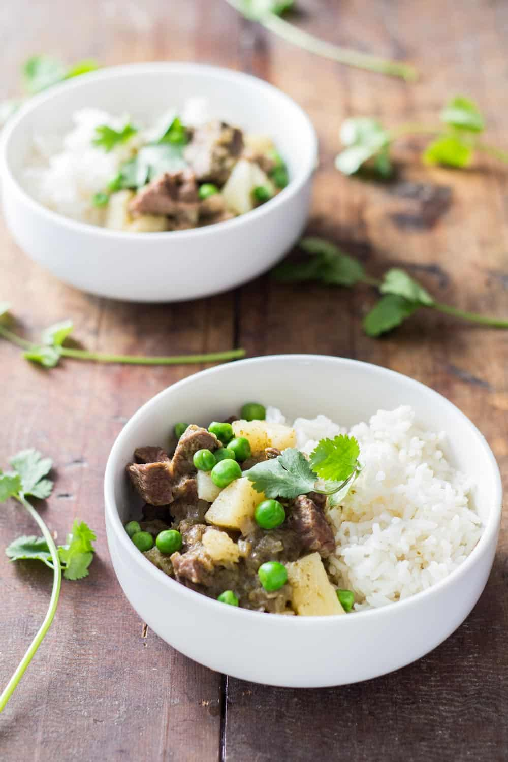 Two bowls of Peruvian Lamb Stew with rice and peas.