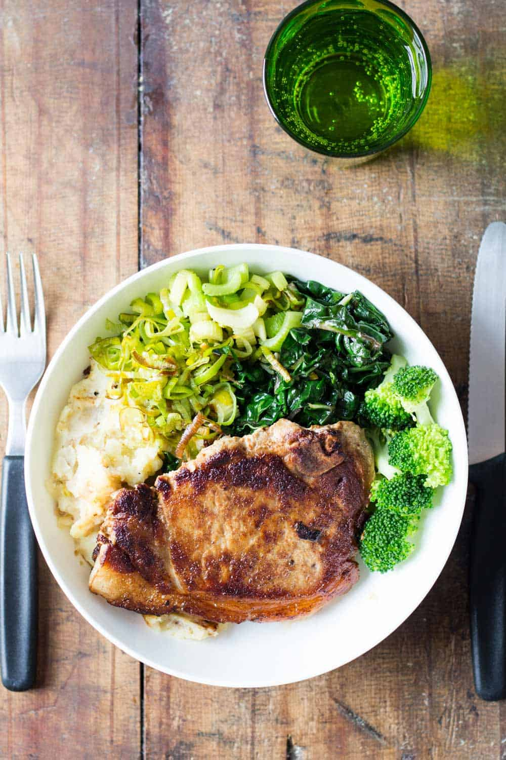 Perfect Pork Chop with mashed potatoes, celery, chard and broccoli, on a wooden table with a fork and knife, and a glass of water.