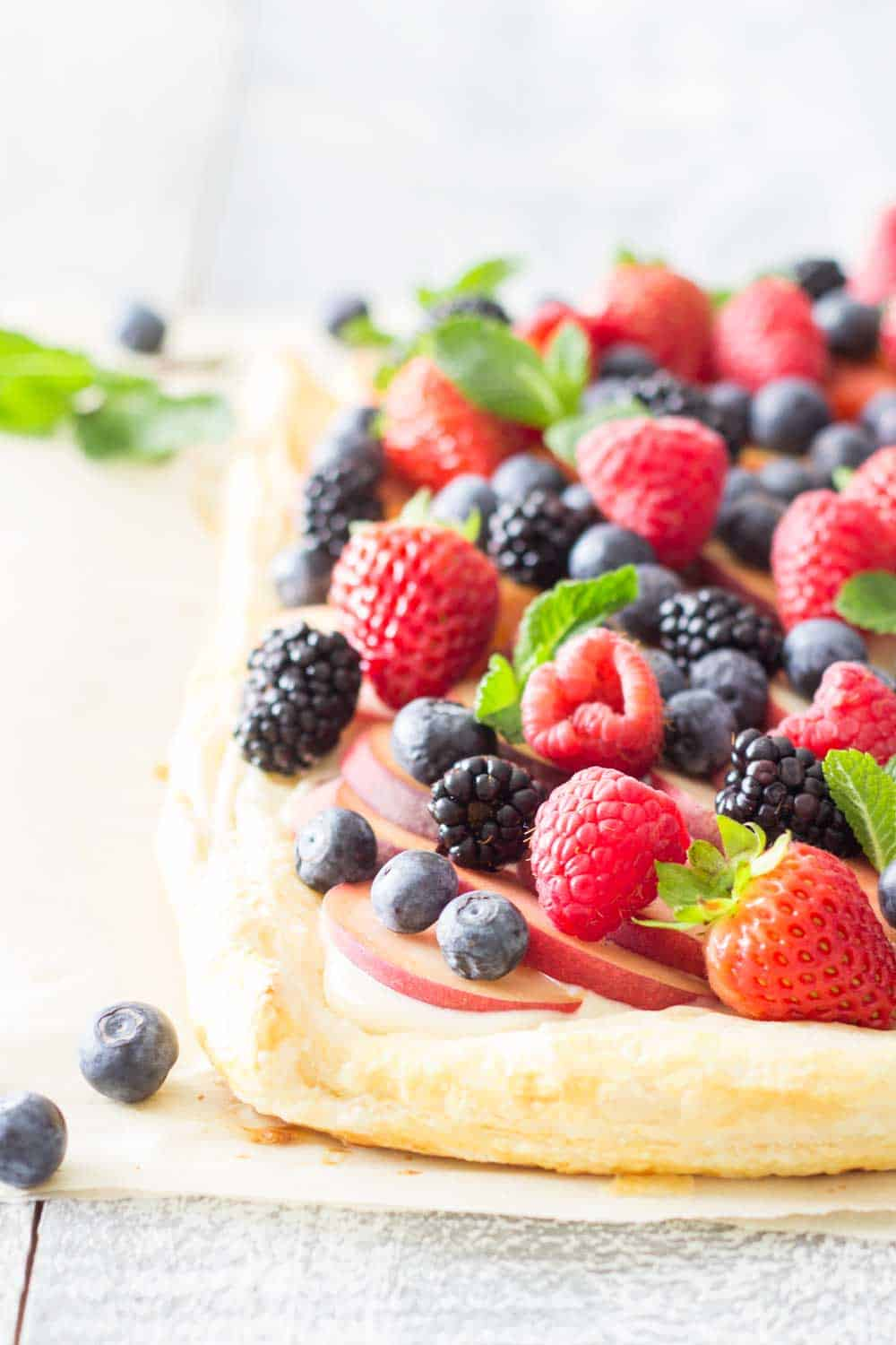 Close up of Summer Fruit Tart with peach slices, blueberries, blackberries, raspberries, and strawberries, to show texture.