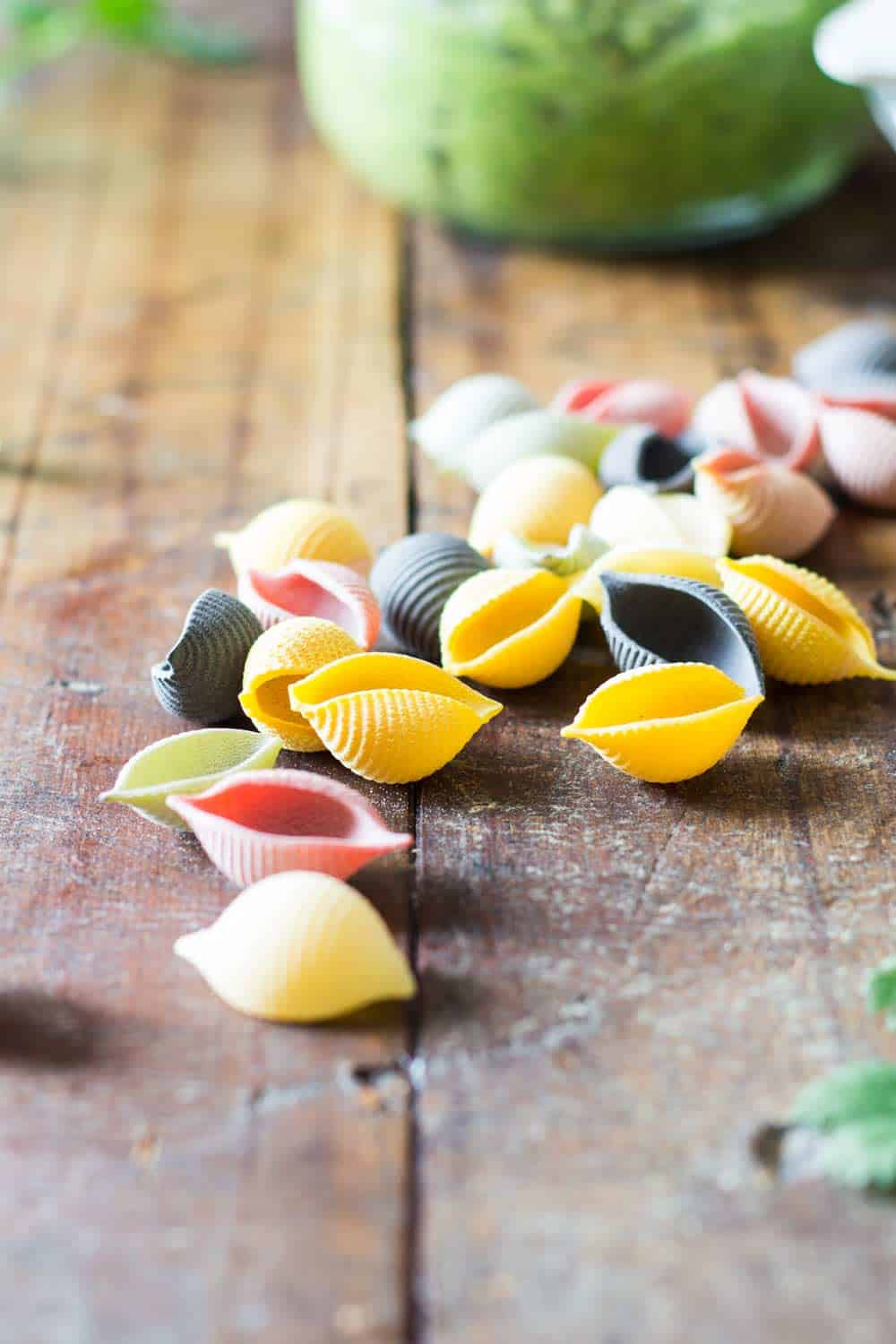 Close up of raw rainbow shell pasta on a rustic wood table.