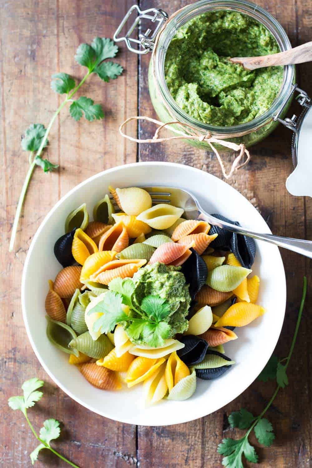 Top view of bowl of rainbow shell pasta topped with Cilantro Pesto, and a jar of Cilantro Pesto with a wooden spoon.