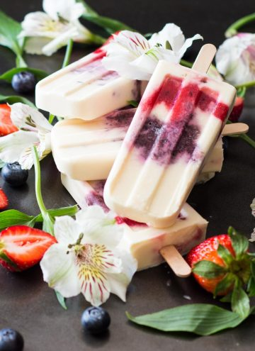 Close up of Greek Yogurt Berry Popsicles laid in a pile with fresh flowers, strawberries and blueberries.