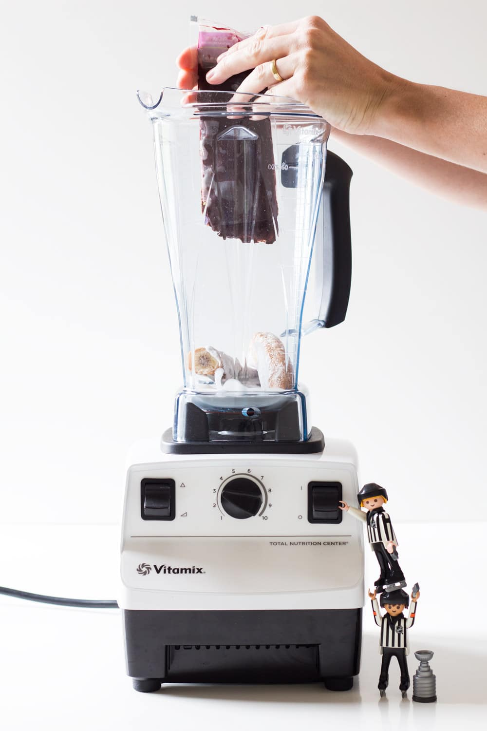 Hands squeezing acai pulp into a blender. Two toy plastic men climbing on the blender.