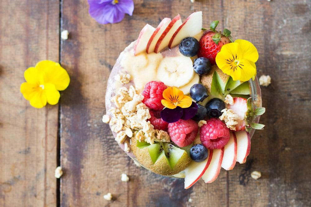 Top view of Acai Bowl topped with fresh fruit and flowers, on a rustic wood table with flowers.