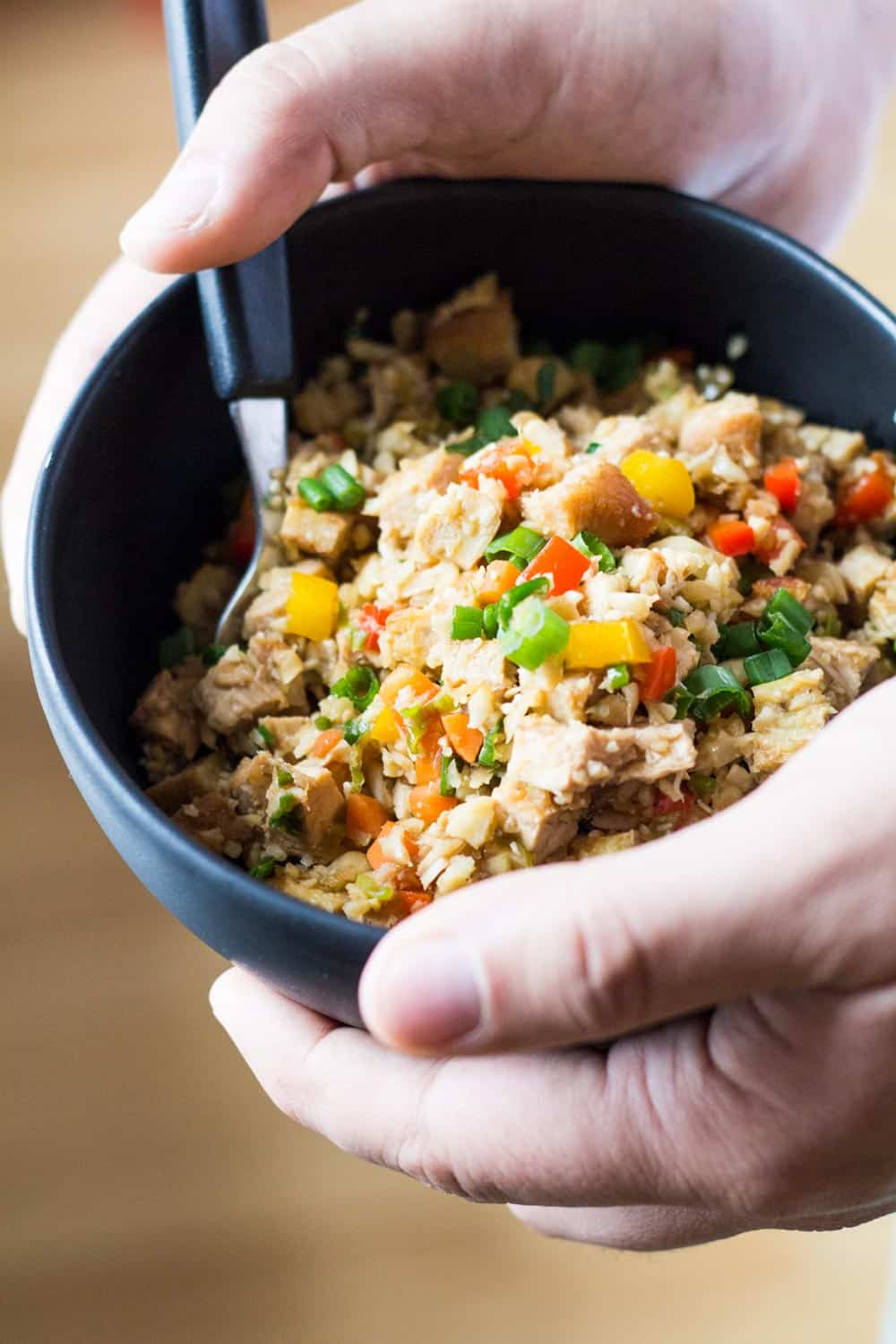 Close up of hands holding a bowl of Cauliflower Fried Rice with a spoon.